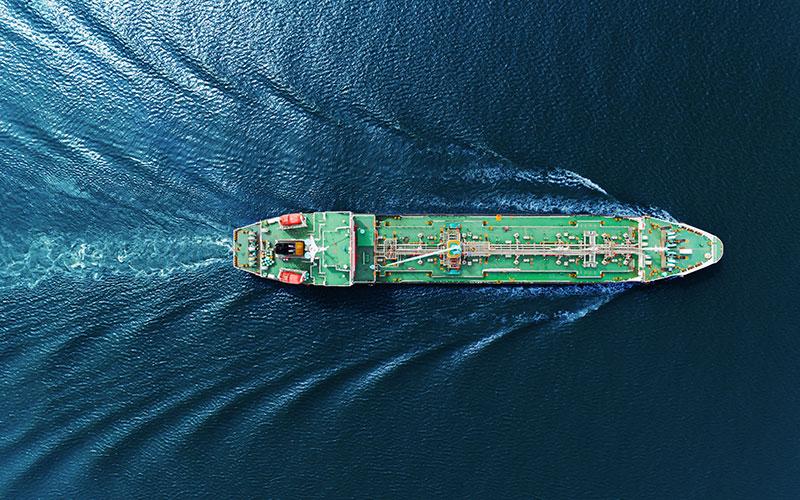 Grönt, stort fartyg på havet.