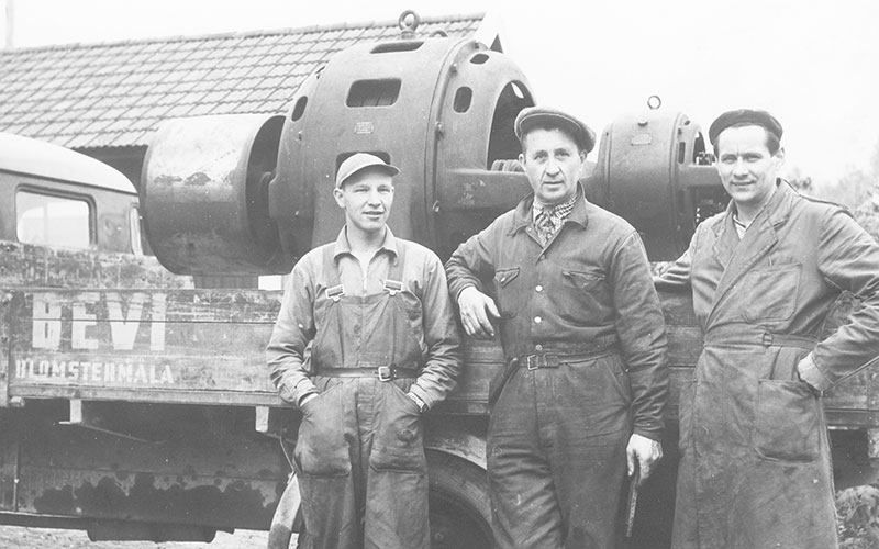 Kolme miestä työvaatteissa kuorma-autolla, jossa oli suuri sähkömoottori tasossa, noin 1940.